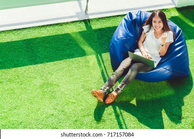 Young cute Asian girl celebrate with notebook laptop, sit on bean bag in garden, copy space on green grass. Success small business, modern lifestyle, information technology, or online shopping concept