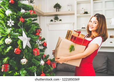 Young cute Asian girl holding X'Mas present boxes, Christmas tree decorated with ornament at home living room. Xmas celebration event preparation, or winter holidays festival indoor party concept