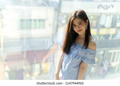 Young cute Asian girl standing near window. Background is Hongdae shopping street in South Korea. Young cute Asian girl portrait concept.