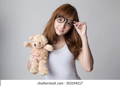 Young cute asian woman  with glasses holding bear doll, Nerd,  loveless or beloved woman concepts,