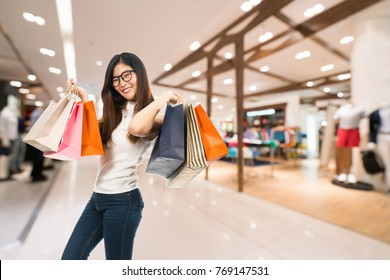 Young cute Asian woman holding shopping bags and smile happily, department store or shopping centre blur background with copy space. Shopaholic, sales promotion event, or modern lifestyle concept