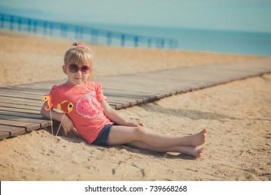 Young cute baby girl enjoying childhood summer time on sandy beach posing on wooden pier bridge wearing casual stylish dress.