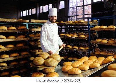 young cute baker smiling pulls out of the oven fresh bread shovel bread