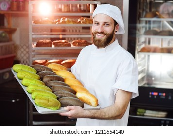 young cute Baker in white uniform holding a tray with colored rolls for hot dog on the background of bakery or bread factory