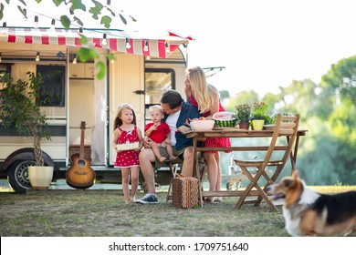 Young cute barefooted family of four having picnic at camping with trailer, camp fire, guitar and dog in summer vacations near the river