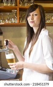 young cute barmaid tapped and holding beer