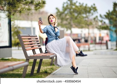 Young cute blond girl with short hair and bright pink lips sitting on a wooden bench making a selfie with kissing lips on her smartphone  wearing denim blue shirt, grey tulle skirt, and black sneakers