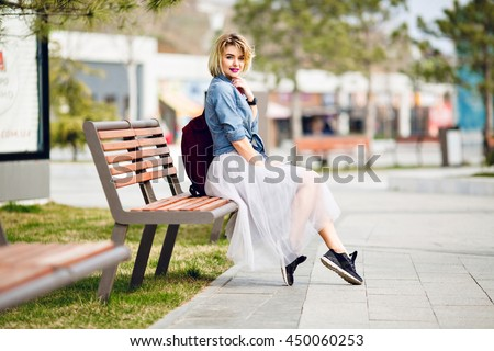 Young cute blond girl with short hair and bright pink lips sitting on a wooden bench and smiling wearing denim blue shirt, grey tulle skirt, black sneakers and marsala backpack