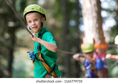 Young cute blond smiling child boy in safety harness and helmet attached with carbine to cable moves along rope way on bright sunny bokeh background. Sport, game, leisure, outdoor activity concept.
