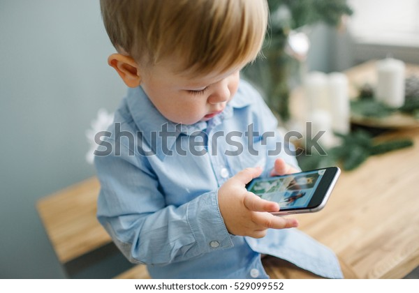 Young cute blonde baby boy with smartphone in christmas decorated room