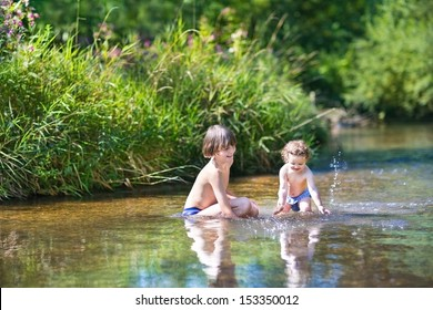 Young cute boy and his little baby sister playing in the water in a beautiful river on a sunny summer day