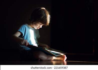 A young cute boy reading a book sitting on the floor on the black background.