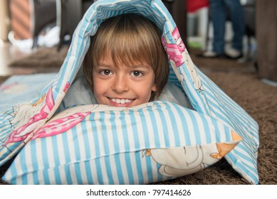 Young cute boy smiling, hiding in the bed sheets made for baby brother on the floor playing