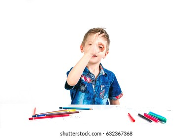 Young cute boy wearing a blue shirt with colored pencils on a white background. The concept is excellent, everything is fine