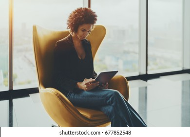 Young cute Brazilian probationer using digital tablet to prepare for interview while sitting in yellow armchair, pensive afro american girl working on digital pad in office settings near huge window