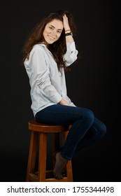 Young cute brown-haired woman in a white shirt and blue jeans sits on a chair in the studio on a dark background and smiles. Beautiful long curly hair. Poses on camera and touches hair. Fashion & Styl