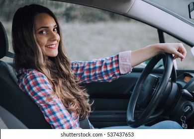 Young cute brunette driving a car