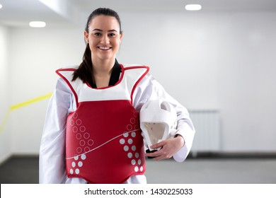 Young cute brunette girl wearing protective martial art gear for taekwondo and smiling