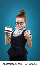 Young cute caucasian girl showing hold credit card. Isolated on blue background