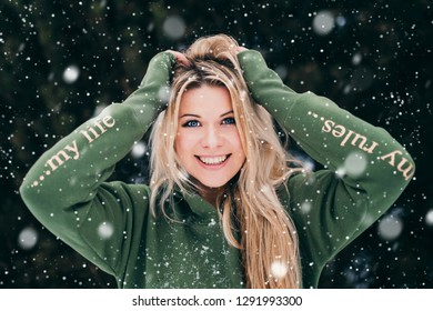 Young cute charming girl with true emotions enjoying snowfall on the forest - expressing positivity and smiling to camera - joyful and cheerful mood - happy winter time