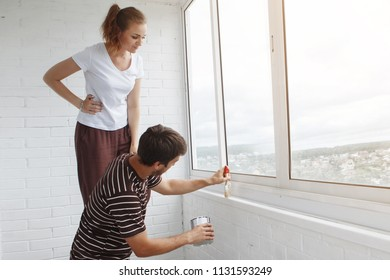 Young cute couple during a renovation in a new building. The guy with the beard paints the window, his wife watches and prompts.