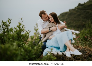 Young cute couple honeymoon on a white chair holding their hands on dating in a beautiful place italy near ocean and mountains, hug, smile and talk to each other