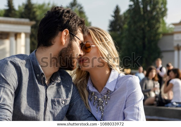 Young cute couple is kissing on the park background on a beautiful sunny summer day, close-up.
