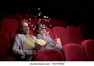 Young cute couple sitting alone at red movie theatre and having fun
