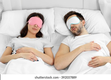 Young cute couple sleeping in eye masks.