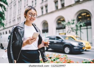 Young cute emotional asian female blogger in glasses for eye protection enjoying strolling around city streets with device and drink.Happy hipster girl sincerely laughing while walk at urban setting