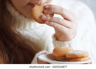 Young cute emotional teenager girl portrait indoor. Eats cookies. Clouse up.