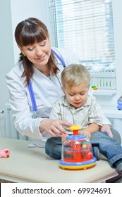 Young and cute female doctor visiting with a stethoscope a little boy