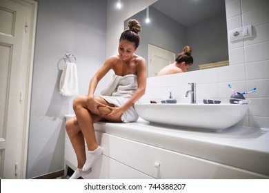 Young cute girl checking cellulite on the leg while sitting on bathroom elements in a towel before showering.
