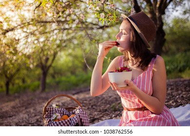 Young cute girl eats strawberry in the middle of blooming garden
