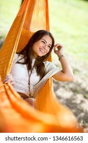Young cute girl enjoy in orange hammock in woods