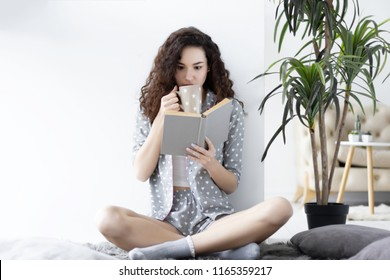 Young cute girl female woman wearing pajamas sleepwear with white hearts sitting on the carpet in light interior room and drinking cup of coffee / tea, reading book. Morning leisure weekend concept