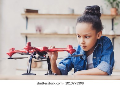 Young cute girl holding quadcopter. Child playing with drone at home. Education, home studying, children, technology, science, future and people concept
