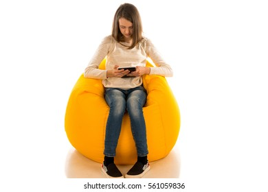 Ordinaire Young Cute Girl Holding The Tablet While Sitting On Yellow Beanbag Isolated  On White Background