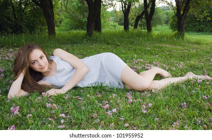 Young cute girl is leaning on the green grass and looking at the camera
