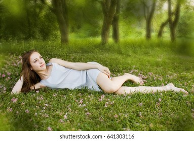 Young cute girl is leaning on the green grass and looks at the sky