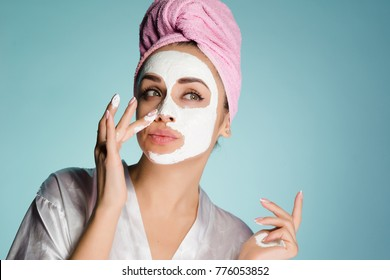 young cute girl with a pink towel on her head puts a white nutritious mask on her face