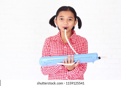 Young cute girl play blue melodeon ,melodies,melodian with happy emotion and smiling.