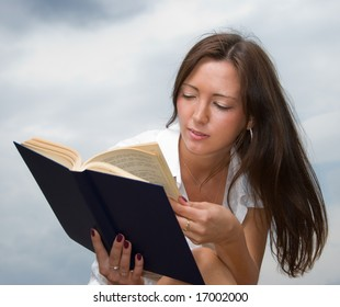 Young cute girl reads a book outdoors