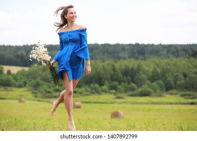 Young cute girl run in a village field at sunset