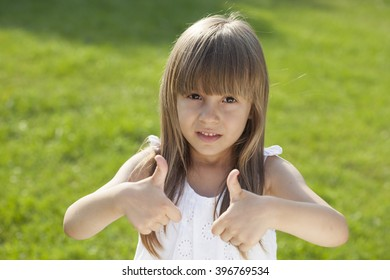 Young cute girl in a white dress in park holding thumbs