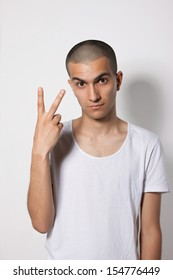 young and cute guy in a white shirt on a light background showing two fingers