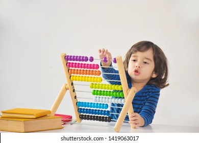 A young cute handsome asian caucasian boy is using the abacus with coloured beads to learn how to count in class - white background and copy space.