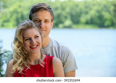 Young and cute happy couple hugging and laughing on river background