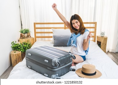Young cute happy lovely Asian girl finished packing suitcase luggage on bed in bedroom, ready to go abroad solo trip. Asia traveler, Asian tourism, or excited tourist pretty woman travel alone concept