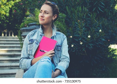 Young cute hipster girl is enjoying beautiful day and recreation time during her spring vacation overseas, pretty female is dreaming about something good while is sitting outdoors in beauty green park